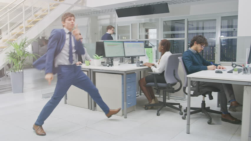 Young Fun Loving and Handsome Businessman Fooling Around, Dances Through the Open Space Office Hallway. Diverse and Motivated Business People Work on Desktop Computers
