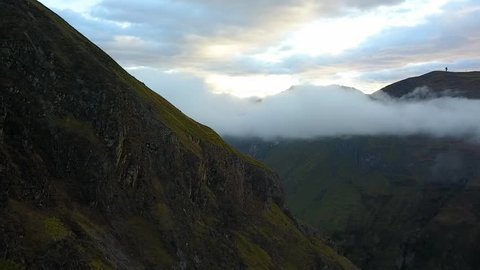 Aerial past a grassy mountain in the Andes with low hanging clouds at sunset