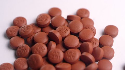 Close-up of a pile of brown ibuprofen pills, spinning left on a white surface