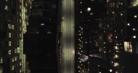 4K aerial video with downward motion and a birds eye view of the dark rooftops of financial- and apartment buildings and an illuminated empty street at night in downtown Oslo, Norway.