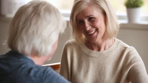 Fifty year old romantic couple elderly spouses sitting together close to each other talking close up focus on pretty blond woman in love look at beloved man smiling showing devotion caress and support