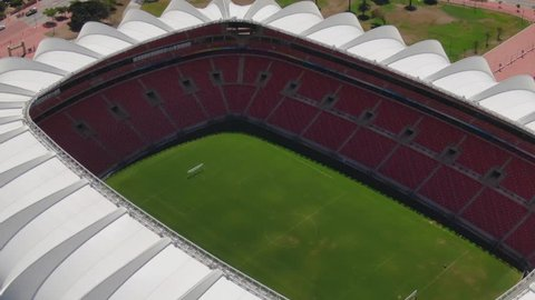 Port Elizabeth, South Africa - circa 2010s: Nelson Mandela Bay Stadium. Top view, pull back to see wide view of stadium in heart of industrial area, next to lake and ocean with ships at sea