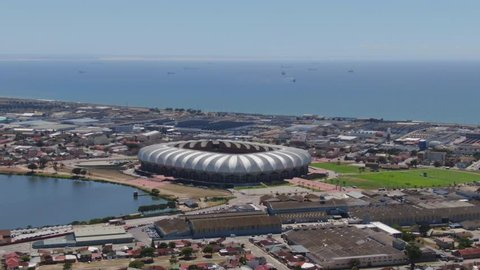 Port Elizabeth, South Africa - circa 2010s: Aerial view, fly forward toward Nelson Mandela Bay Stadium in the middle of industrial area and next to lake. See ships waiting at sea in the bay