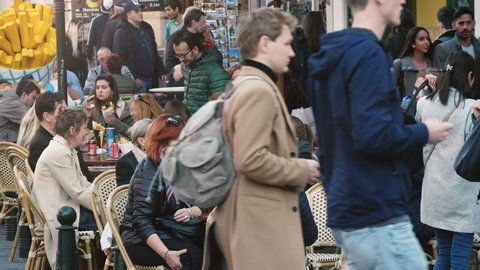 Bruges, Belgium - March 31, 2019:Exciting view of jolly young people drinking coffee and telling funny stories in a crowded street in Brussels in spring in slow motion