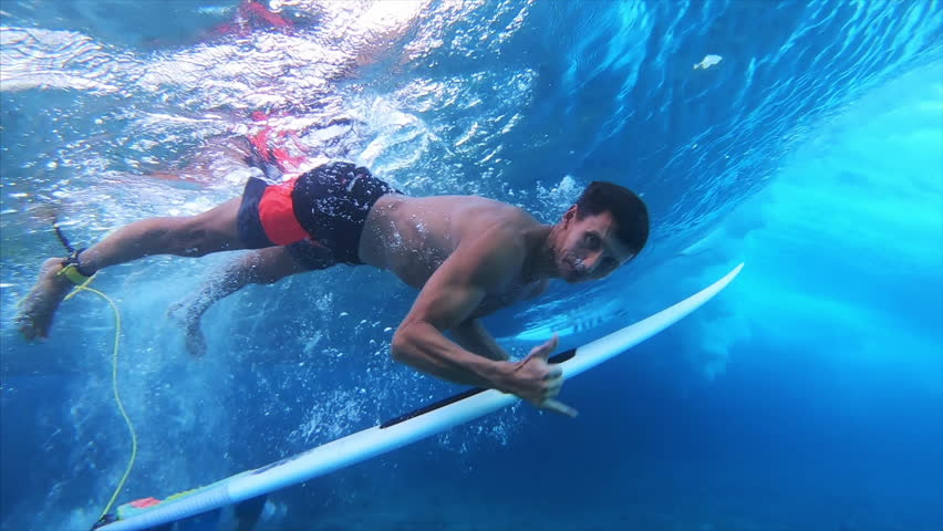 Surfer dives under the wave with the surfboard (the trick named in surfing as Duck Dive) looks into the camera and shows the Shaka sign