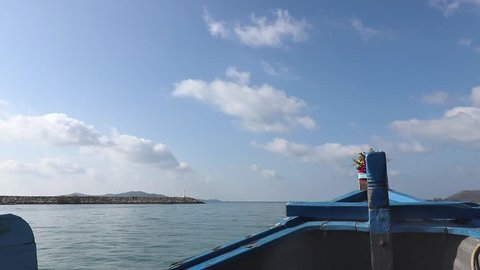 A panning shot from left to right on a ferry boat showing the bow and the horizon in front of the boat. In the distance it can be seen some rocks formations and Samet Island ,Thailand.