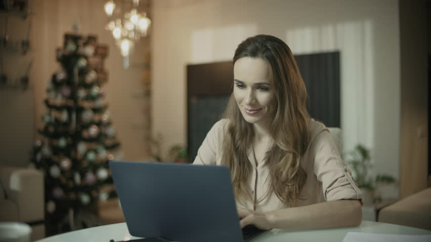 Young woman working on laptop computer at christmas home. Female person looking laptop screen at xmas home. Beautiful entrepreneur working online. Serious professional using internet at holiday | Shutterstock HD Video #1028232842