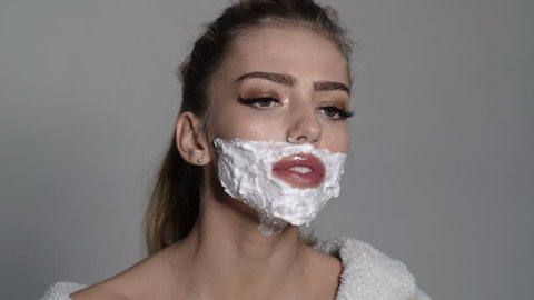Lady shaves her face with sharp blade of straight razor. Woman with face covered with foam holds straight razor in hand. Barber and shaving concept. Girl on busy face wears bathrobe, grey background
