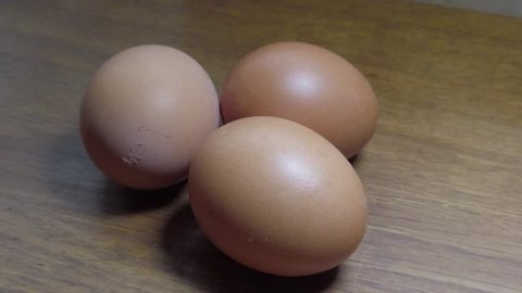 Slow motion hands taking or placing group of brown eggs onto clean wooden natural kitchen surface.