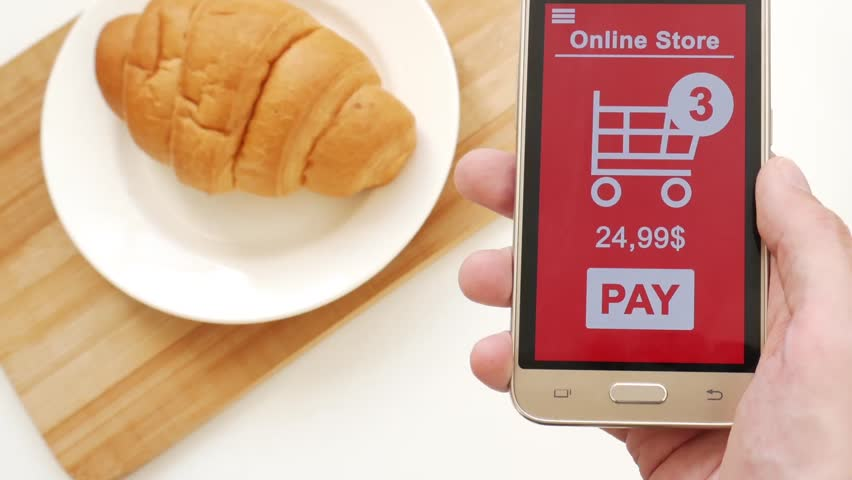 Buying in the online store through the phone during breakfast | Shutterstock HD Video #1028255522