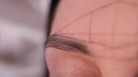 Close-up. Makeup artist draws eyebrow with a pencil before of permanent makeup.