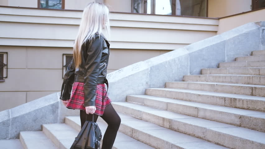 Young blonde woman going up stairs. Happy urban chic lady running with skirt flying. Friends meeting date leisure walk.