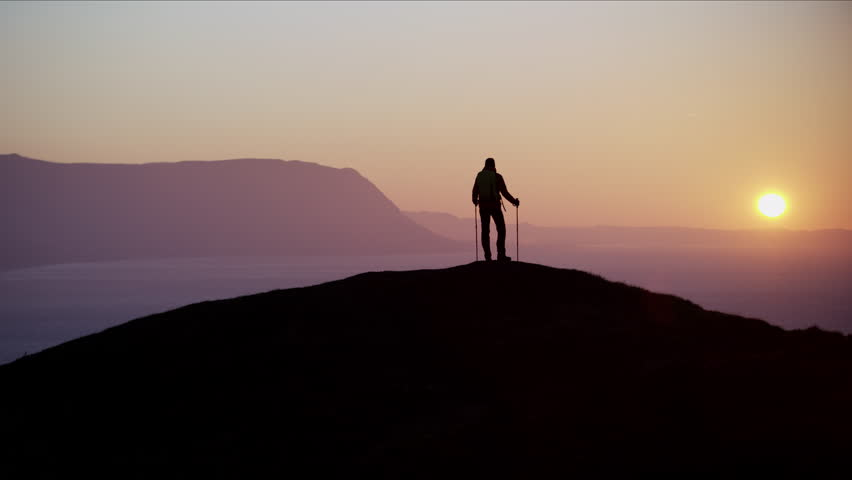 Silhouette of fit Caucasian European female hiker with Nordic poles enjoying trekking at sunrise Snowdonia National Park Wales RED MONSTRO #1028325722