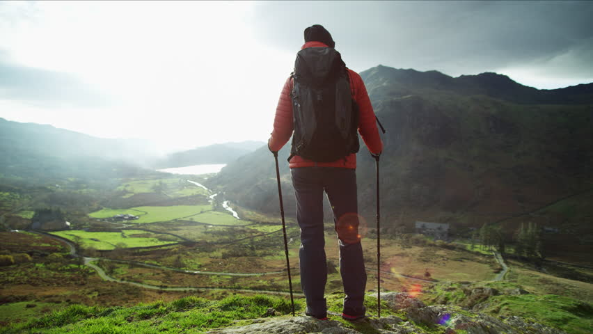 Fit female adventure tourist with rucksack and Nordic walking poles on her vacation trekking nature Snowdonia National Park Wales RED MONSTRO | Shutterstock HD Video #1028326172
