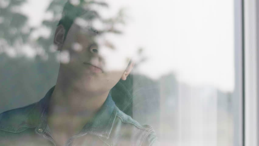 Asian boy is sad looking out the window, The boy face close up child through the glass. Sad boy looks out the window. 60fps | Shutterstock HD Video #1028344352
