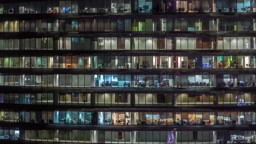 Working evening in glass business centre office building with numerous offices with glass walls and illuminated windows timelapse. People sitting at desks. Pan right #1028367182