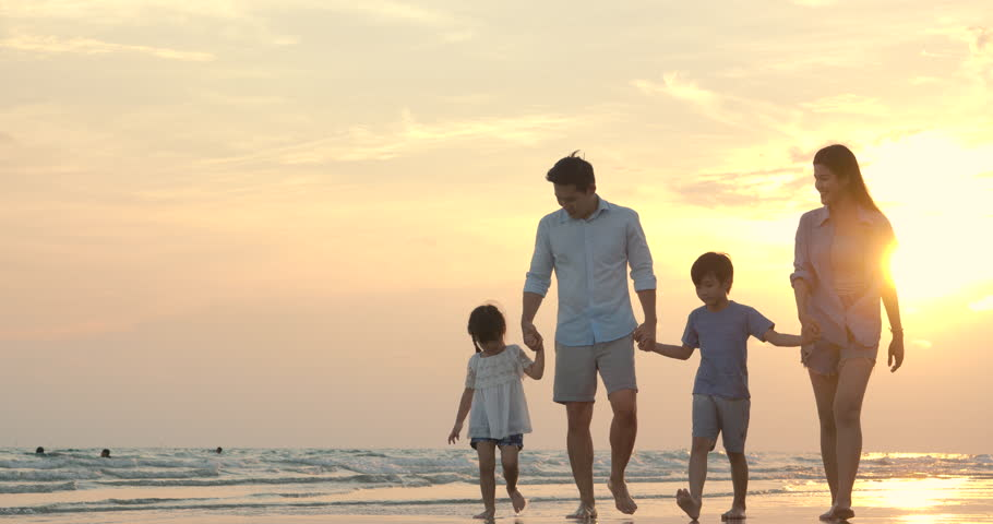 Happy asian family walking down the beach at sunset on summer vacation. Slow motion. Family, Holiday and Travel concept. | Shutterstock HD Video #1028374772