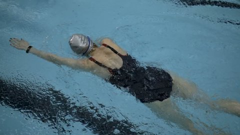 Top view of female amateur swimmer doing front crawl in swimming pool, Slow motion, Full HD steady shot