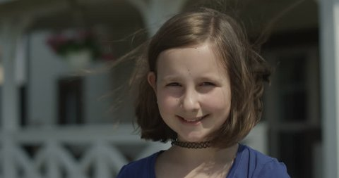 Portrait of a child girl with choker looking at the camera and smiling  outdoors on sunny day at the house porch of terrasse shot on red