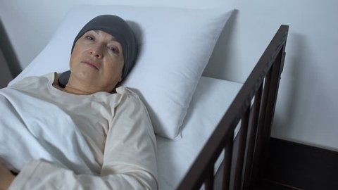 Hopeless female patient suffering cancer lying in sickbed and looking at camera