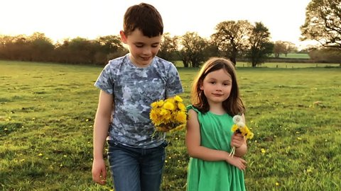 2 young children skipping through spring fields holding dandelions