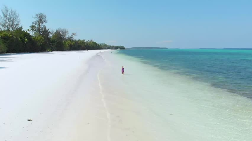 Aerial slow motion: woman walking on white sand tropical beach turquoise water coral reef Pasir Panjang Kei Islands Maluku Moluccas archipelago Indonesia | Shutterstock HD Video #1028495762