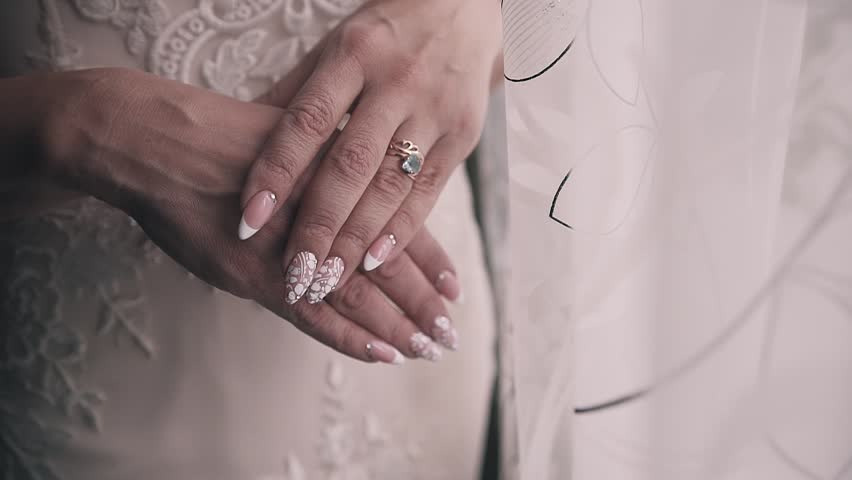The woman in the white dress folded her hands in front of her. She has a pedicure on her nails and a ring on her left hand. Close-up of female hands.