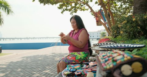 Indigenous woman of Kuna Indians from Darién province, Panama making traditional handicraft, object, tourist souvenir in urban park of Panama City. Native lady of Central American tribe sewing