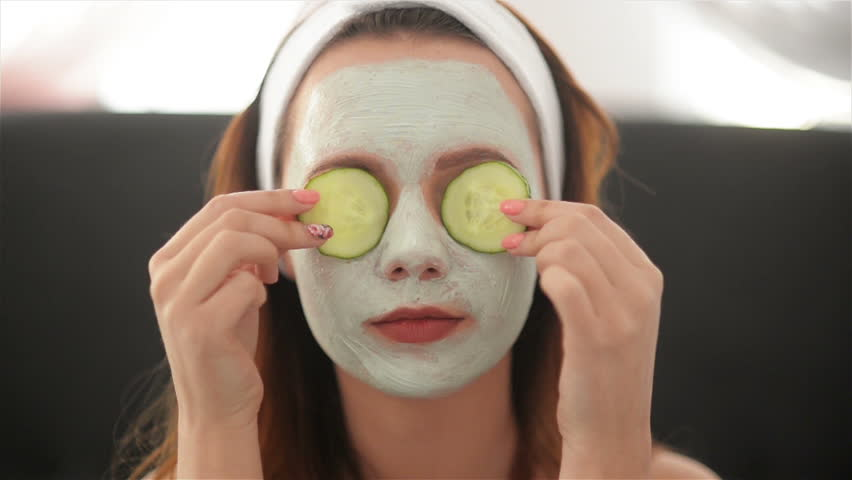 Close Up of a Girl With a Mask On Her Face And a Towel On Her Head That Closes Her Eyes With Cucumbers And Smiles. Woman Wearing Face Mask. Face Care Concept | Shutterstock HD Video #1028569712