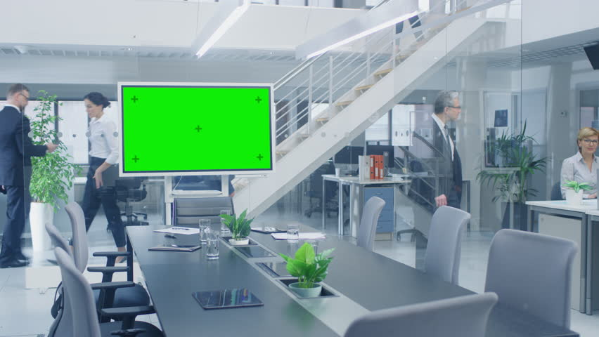 In the Corporate Office Meeting Room Stands Green Mock-up Screen TV or Interactive Digital Whiteboard in Horizontal Mode. In the Background Big Bright Busy Office with Businesspeople Working   Shutterstock HD Video #1028612102
