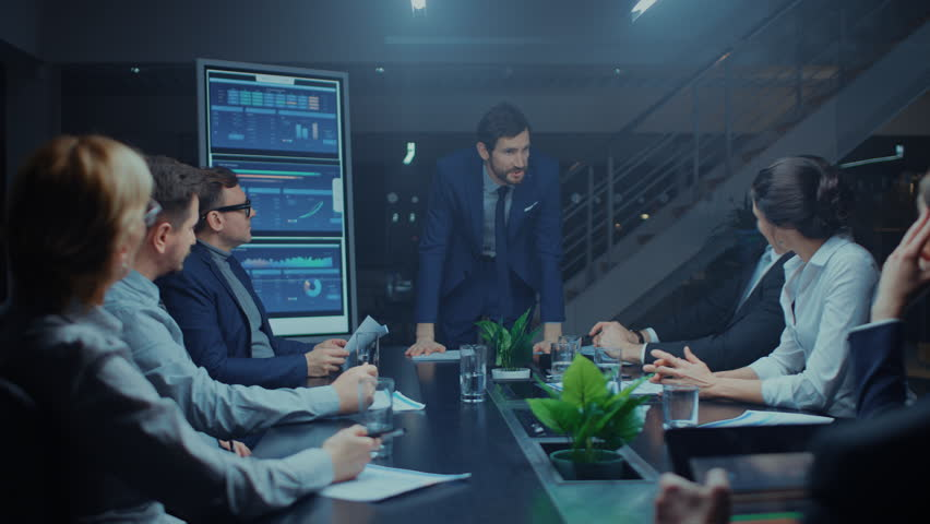Late at Night in the Meeting Room: Handsome Executive Director Stands in the Head of the Conference Table Leans on it and Delivers Eloquent Speech to a Group of Businesspeople and Investors. | Shutterstock HD Video #1028612462