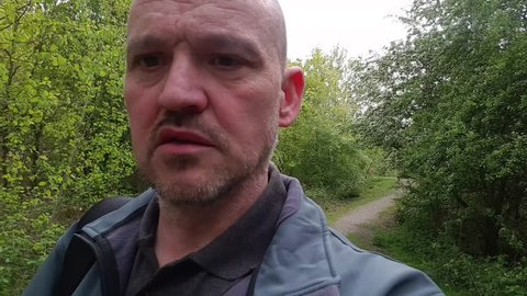 close up POV of a white male with short hair and stubble lost in the woods searching for a way out.