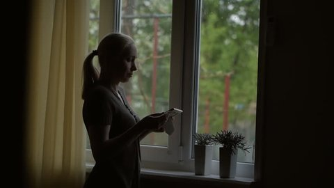 Standing at the window, a woman holding a picture in a frame, looking at her and stroking his hand.