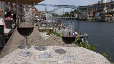Porto, Portugal - April 29, 2019: Red, white and Porto wine glasses overlooking tourists at Cais da Ribeira and Ponte de Dom Luis I on the River Douro in Porto, Portugal. Live accoustic guitar music