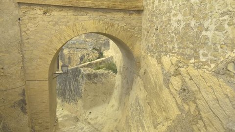 Close up shote of a gate on castle in Alicante, Spain. The camera pans slowly to the left,  angled down a sloping walkway.