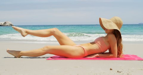 Side view of Caucasian woman relaxing in hat on the beach. Beautiful sea waves in the background