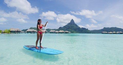 Paddleboard woman relaxing at Bora Bora luxury hotel resort vacation in Tahiti, French Polynesia. Asian bikini girl having fun watersport activty by Mount Otemanu summer holiday.