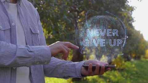 Unrecognizable man shows conceptual hologram with text Never give up. Farmer on the background of the apple orchard in casual clothes with the technology of the future mobile screen
