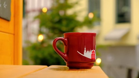 Hot Steaming Gluhwein Mug at a Christmas Market in Germany, With Christmas Tree on the Background