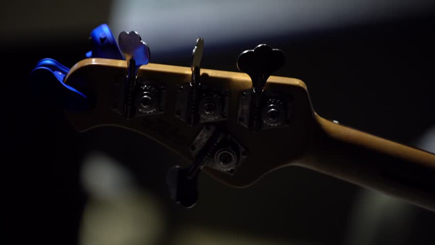 Close-up: guitar neck bass guitar with metal pegs, shooting from the back | Shutterstock HD Video #1028799662