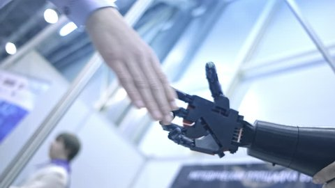 Future is now. Male hand of young student scientist inventor shakes robotic arm. Hand of a man shaking hands with robot. Robotic and human hands join in a handshake