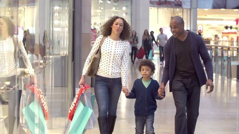 Family walking through shopping mall carrying sale bags looking at window displays.Shot on Sony FS700 at frame rate of 100fps