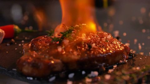 Close-up view of juicy cooked slice of meat and fresh vegetables with flames. bbq burn original recipe of dish. Professional cooking, exotic meal cook recipe, preparing food. Slow motion