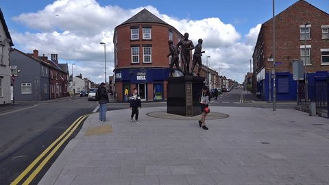 "Liverpool, UK. May 4th 2019. A Boy playing football by the statue to commemorate Colin Harvey, Alan Ball and Howard Kendall ""The Holy Trinity"" at Goodison Park, Everton, shot in slow motion 250fps."