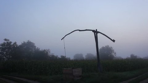 Still timelapse of a shadoof in the foggy morning.