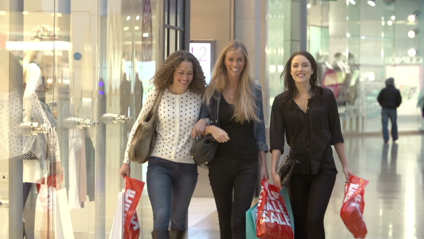 Three young women walk arm in arm through shopping mall carrying sale bags.Shot on Sony FS700 at frame rate of 25fps | Shutterstock HD Video #10288853