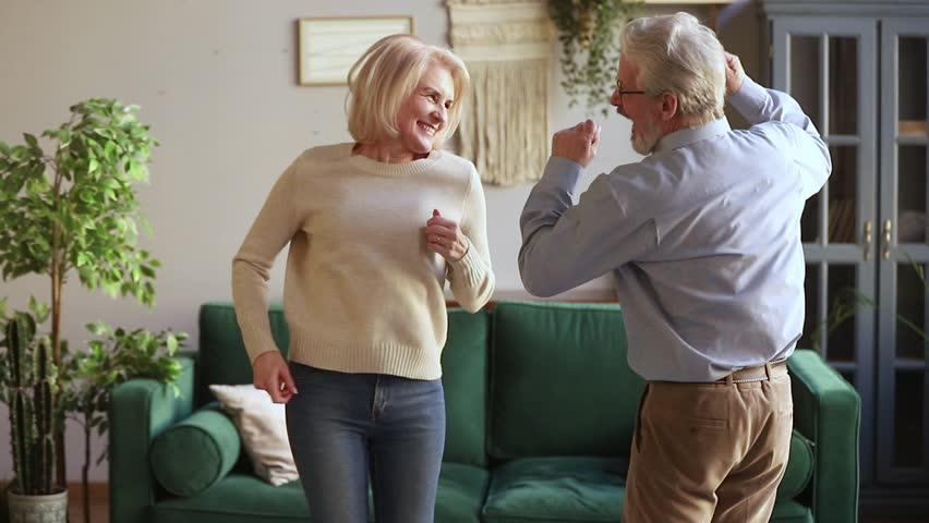 Happy carefree old senior couple jumping to music dancing laughing in living room, active cheerful aged mature spouses having fun together at home celebrating anniversary enjoying leisure lifestyle