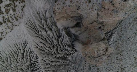 Aerial drone scene of eroded slope in mountainous landscape. From top of abstract natural erosion drawings to general view of eroded hill. Coranzuli, Salta, Argentina
