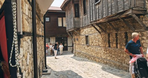 NESSEBAR, BULGARIA - JULY 2018: People walk through pedestrian cobblestone streets of ancient Nessebar with cafe, restaurant and souvenir shops at sunset.