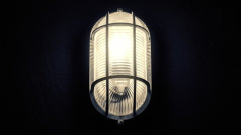 A scary flickering light lamp inside a basement, turning on and slightly off because of the unstable electrical current (or a paranormal phenomenon).